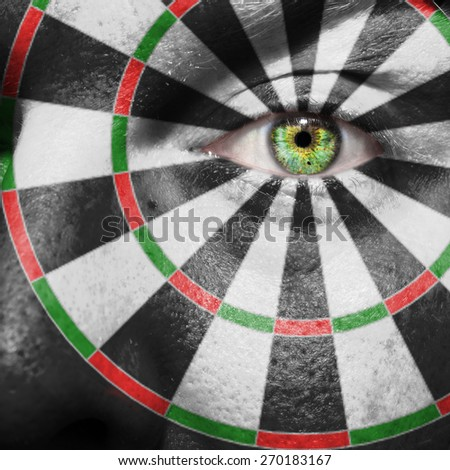 Dartboard painted on a man's face to support the game - stock photo