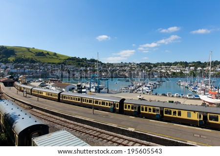 Dartmouth and Kingswear train station with colourful yellow carriages on railway track by marina with boats with blue sky and clouds in Devon England by the River Dart  - stock photo