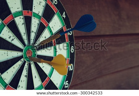 Darts arrows in the target center. Shallow depth of field. Toned. - stock photo
