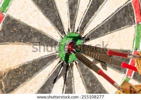 Darts board with three arrows in bullseye - stock photo
