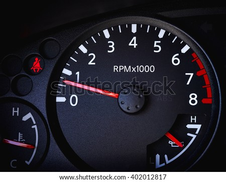 Dashboard of a car showing tachometer, partial speedometer, temperature gauge, battery guage, seat belt warning light and open door warning light - stock photo