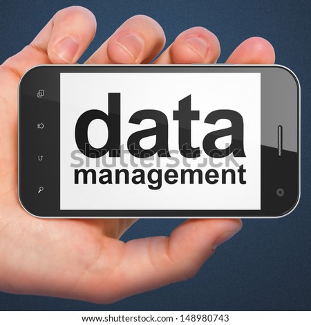 Data concept: hand holding smartphone with word Data Management on display. Generic mobile smart phone in hand on Dark Blue background. - stock photo