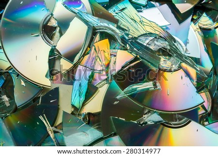 Data destruction: stack of broken CD and DVD disks - stock photo