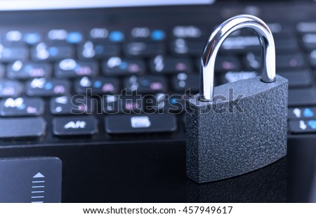 Data security concept with padlock on laptop computer keyboard. Toned in blue - stock photo