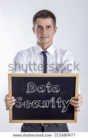 Data Security - Young businessman holding chalkboard with text - stock photo