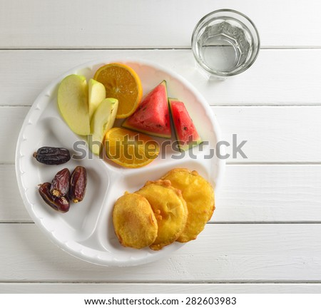 Date, fresh fruits and fried snacks. A food commonly consumed while breaking fast during holy month of Ramadan. - stock photo