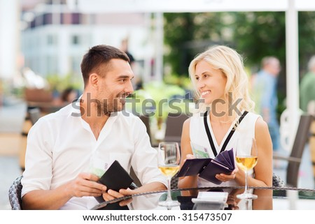 date, people, payment and financial independence concept - happy couple with cash money in wallets and wine glasses paying bill at restaurant - stock photo