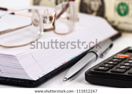 Datebook, metallic pen, black calculator, glasses and dollar note - stock photo