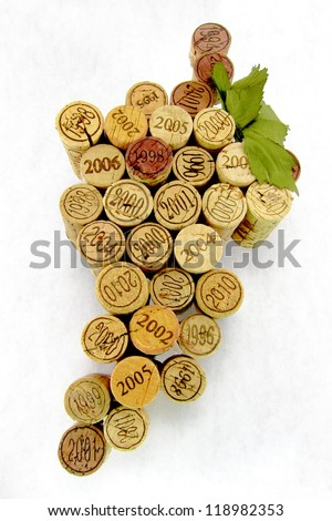 Dated and vintage wine corks in the shape of a group of grapes with a green leaf on white background. - stock photo