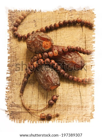 dates and islamic rosary image on papyrus paper texture - stock photo