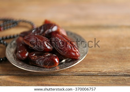 Dates fruit and rosary on wooden background, close up - stock photo