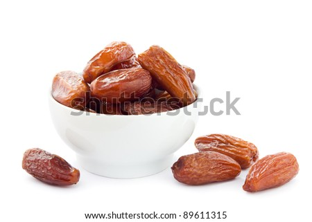 Dates in a white bowl on a white background. - stock photo