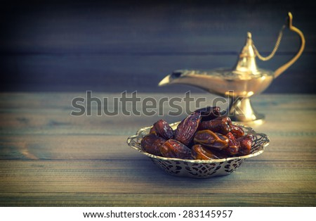 Dates in golden bowl and arabian Aladdin lamp on wooden background. Vintage style toned picture - stock photo