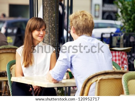 Dating couple enjoying the outdoors in a Parisian cafe - stock photo