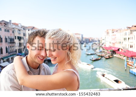 Dating couple hugging and kissing in Venice on travel together. Young happy couple on holidays or honeymoon having cute romantic vacation together in Venice by Grand Canal on Rialto Bridge - stock photo