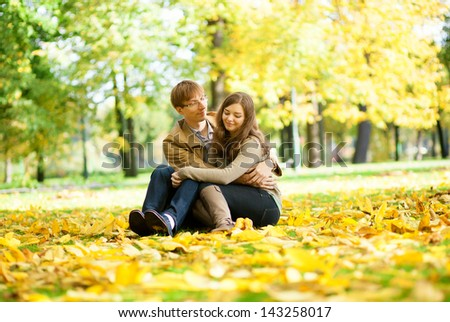 Dating couple in yellow leaves on a fall day - stock photo