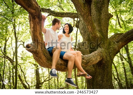 Dating in nature - young couple sitting together on big tree - stock photo