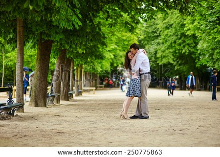 Dating romantic couple hugging in the Luxembourg garden of Paris - stock photo