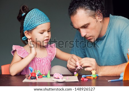 Daughter and dad molded from clay - stock photo