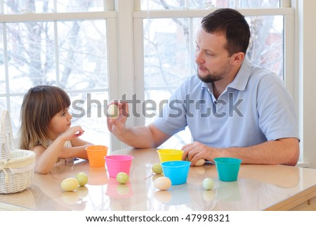 Daughter and father coloring eggs for Easter holiday - stock photo