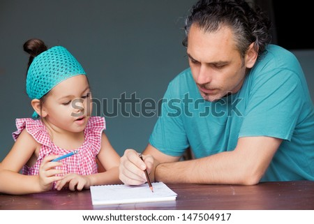 Daughter and father draw and write together - stock photo