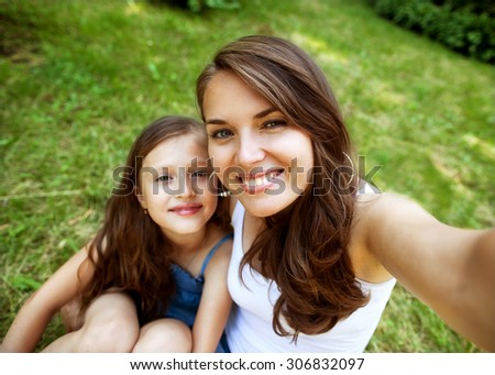 Daughter and mother are doing self park smiling - stock photo