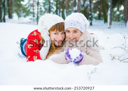 daughter and mother are happy together. Mom and daughter lying on the snow in winter - stock photo
