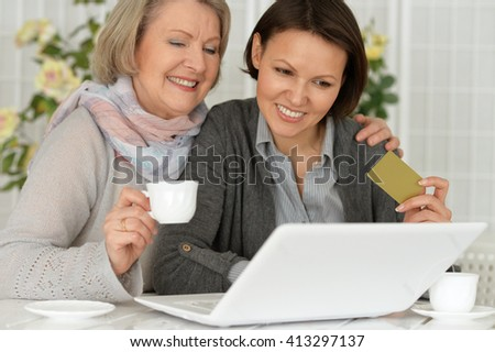 daughter and mother are shopping on the Internet with a credit card - stock photo