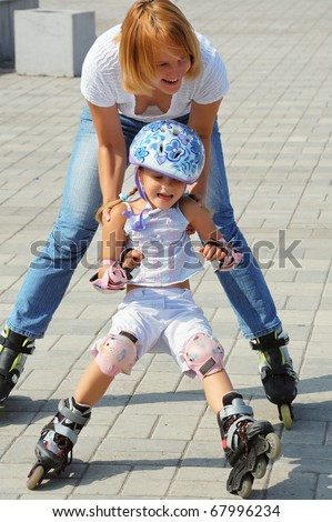 daughter and mother having fun on in-line skates on a sunny summer day - stock photo
