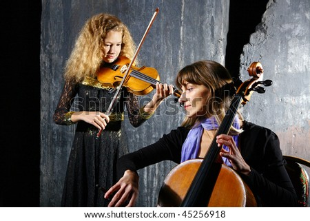 Daughter and mother playing on cello and violin on grey wall background - stock photo