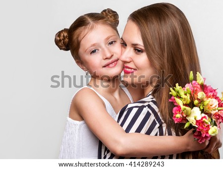 daughter gives her mother flowers in the studio, happy mother's day 	 		daughter gives her mother flowers in the studio, happy mother's day  - stock photo