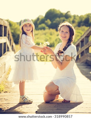 Daughter gives mother flowers on nature. - stock photo