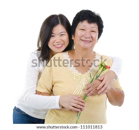 Daughter giving carnation flowers to her mother over white background - stock photo