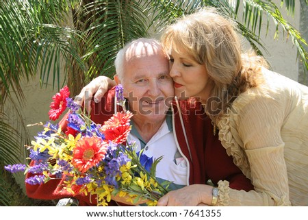 Daughter giving father a hug with flowers upclose - stock photo