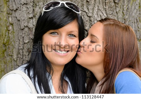 Daughter giving her mother a kiss outdoors teen happy bonding - stock photo
