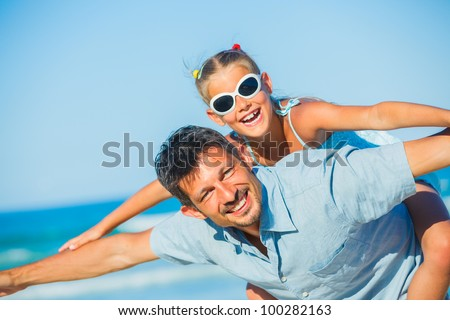 daughter having fun on tropical beach - stock photo