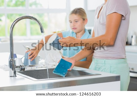 Daughter helping mother do the washing up in the kitchen - stock photo