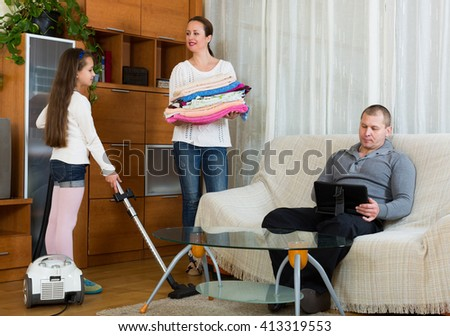 Daughter helping positive mother to clean, father resting on couch - stock photo