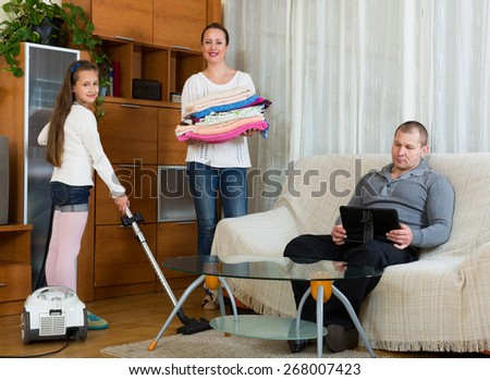 Daughter helping smiling mother to clean, father resting on couch - stock photo