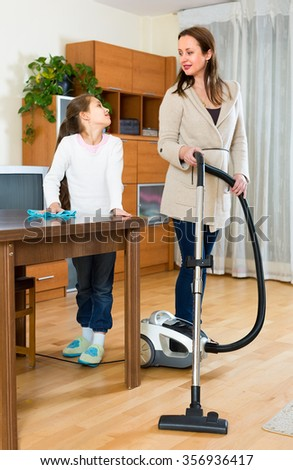 Daughter helps her mother to clean up their apartment. She is wiping of dust from the wooden table while woman is vacuuming the floor - stock photo