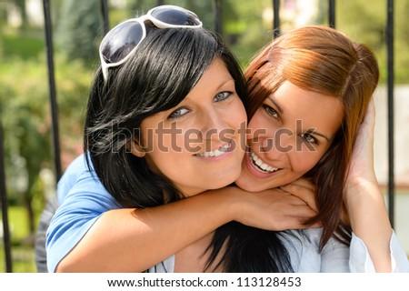 Daughter hugging her mother outdoors happy loving teen bonding affectionate - stock photo