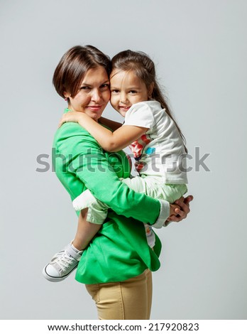 Daughter hugging her mother sitting in her arms - stock photo