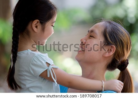 Daughter hugging mother Asian family - stock photo