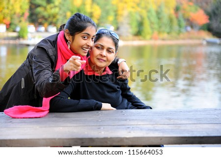 Daughter is showing something to mother in outdoors - stock photo