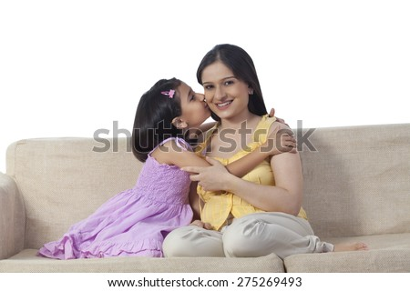 Daughter kissing pregnant mother - stock photo