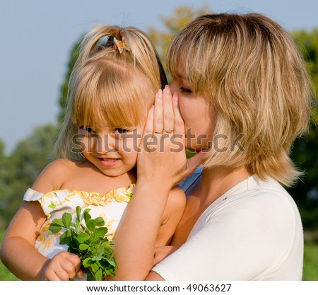 Daughter listening to her mother's secret whispers - stock photo