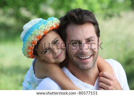 Daughter on Father's back - stock photo