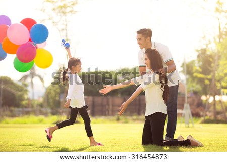 Daughter running to mother She enjoyed the play balloons - stock photo
