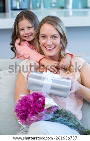 Daughter surprising mother with gift at home in the living room - stock photo