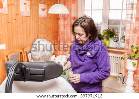 Daughter takes care of her elderly father - stock photo